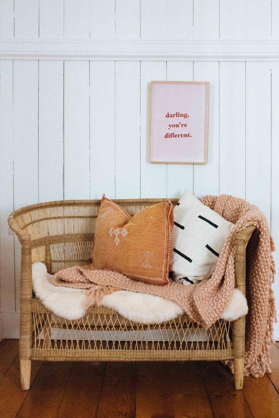 nursery spot consisting of rattan settee blush crochet throw blanket white shag cushion ochree throw pillow