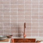 Soft Blush Toned Tile Backsplash With White Grouts Copper Sink And Faucet White Countertop Light Wood Kitchen Cabinets