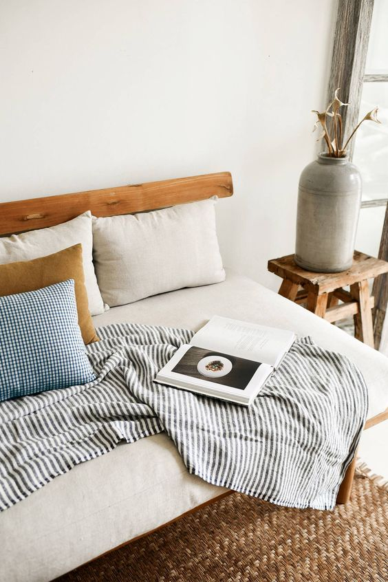 striped throw blanket teak daybed with white cushion and colorful throw pillows woven rug wooden side table with ceramic vase
