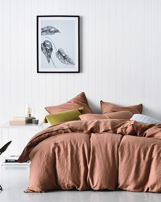 terracotta bedding treatment crisp white wood plank walls crisp white floors black framed floral painting