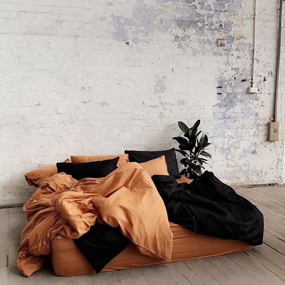 terracotta duvet cover black duvet cover terracotta pillows black pillows whitewashed brick walls light wood plank floors