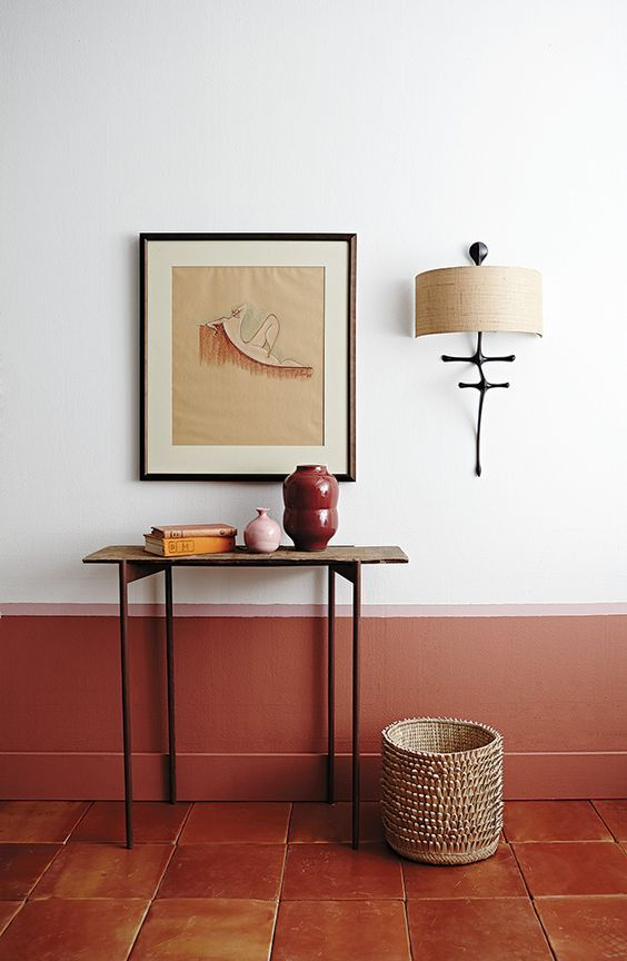 terracotta tiled floors white walls accented with rust color baseboard slim and small console table cream basket