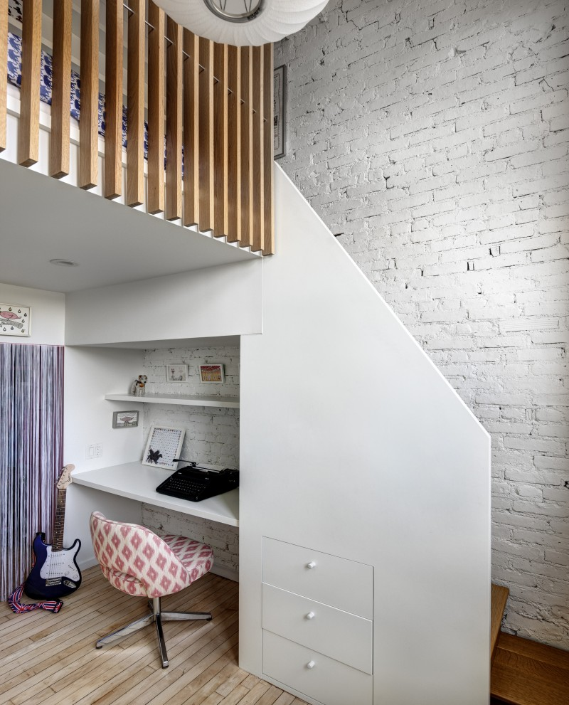 tucked home office next to stairs white floating desk open shelf in white whitewashed brick walls