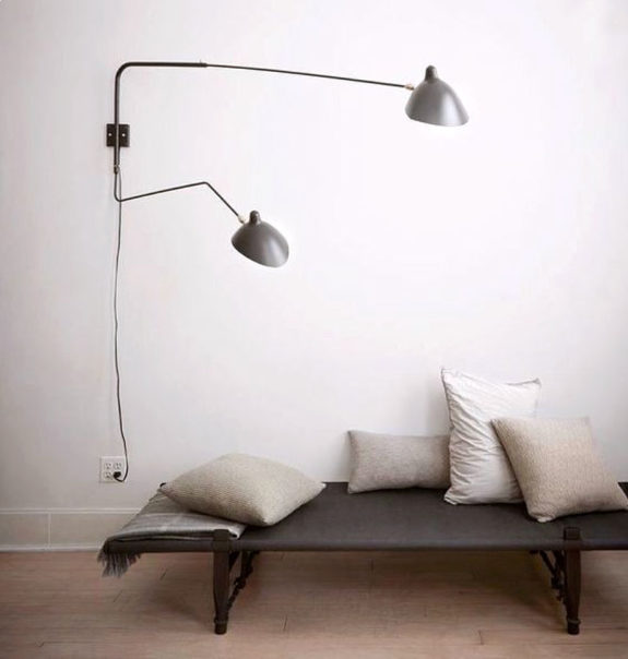 ultra minimalist bench seat in gray some throw pillows in broken white wall mounted lamps with silver lampshades