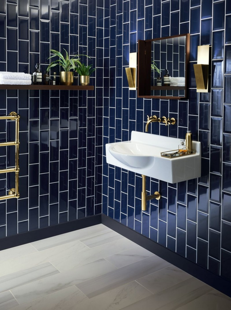 vertical metro tiles walls in deep blue with white grout brass fittings white bathroom sink some house plants