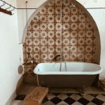 Vintage Bathroom With Recessed Wall Accented With Geometric Tiles And Dome Like Top Claw Foot Bathtub