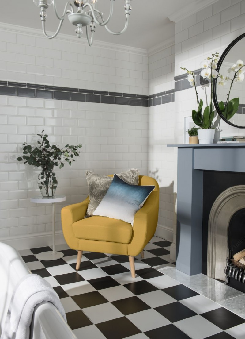 white metro tiled walls with dark gray tile accent sunny yellow armchair monochrome tiled floors