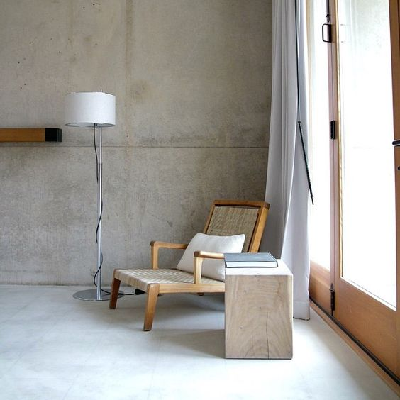 woven lounge chair with wooden frame light toned log side table modern floor lamp with white lampshade stone colored concrete walls dramatic white curtains