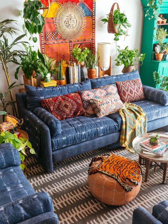 New Bohemian living room deep blue sofa with white accents round top coffee table brown ottoman flat woven area rug lots of greenery