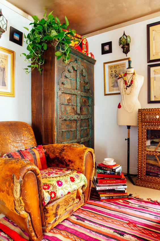 New Bohemian reading nook worn out leather armchair layered pattern area rug antique armoire greenery
