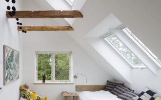 Scandinavian style attic bedroom series of skylight exposed wood beams glass window light wood floors white beanbag with animal stuff