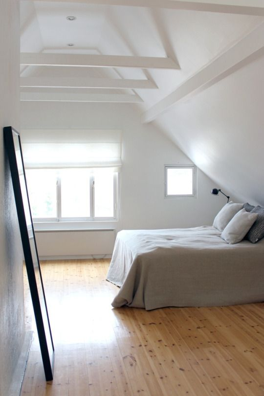 all white bedroom slanted wall and ceiling exposed beams in white light wood floors glass windows white bedding treatment