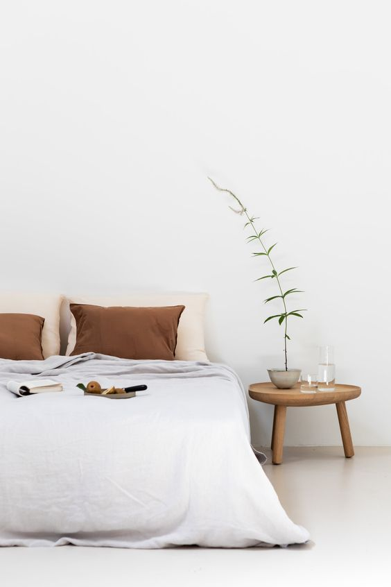 all white interior white bedding treatment with rust colored pillows midcentury modern bedside table tiny houseplant on pot