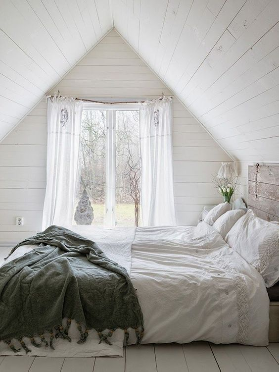 attic bedroom design bed frame with whitewashed headboard dramatically white curtains green duvet cover white wood plank floors walls and ceilings