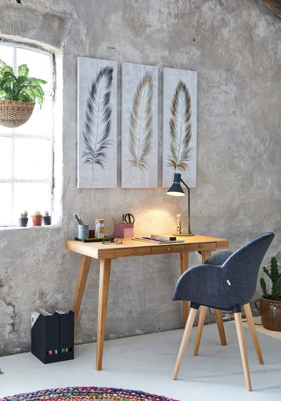 bare concrete walls wood working desk in midcentury modern style working chair in midcentury modern style with dark blue cushion feathers wall decors