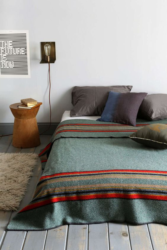 bold blanket with red line accents white shag mat wooden bedside table gray pillows light fixture above the bed