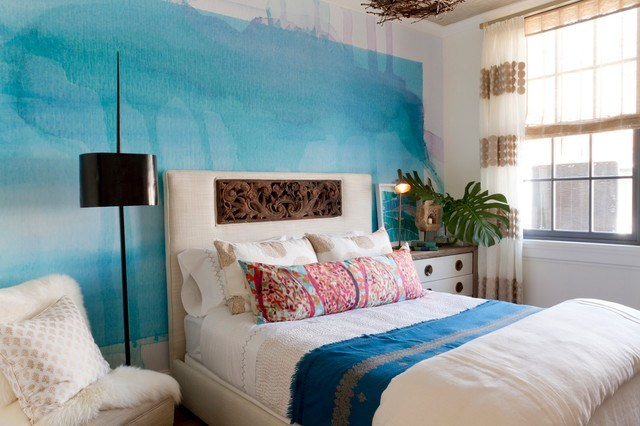 canvas like wall in blue modern bed frame with white headboard accented with traditional wood carvings