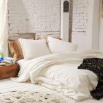 Crisp White Duvet Cover With Pom Pom Fringes Wood Plank Floors In White White Brick Walls Round Shaped Crochet Rug