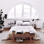 Curved Glass Window With White Trims Wood Plank Floors Floor Bed Wood Bench Bed Potted Houseplant Round Top Bedside Tables