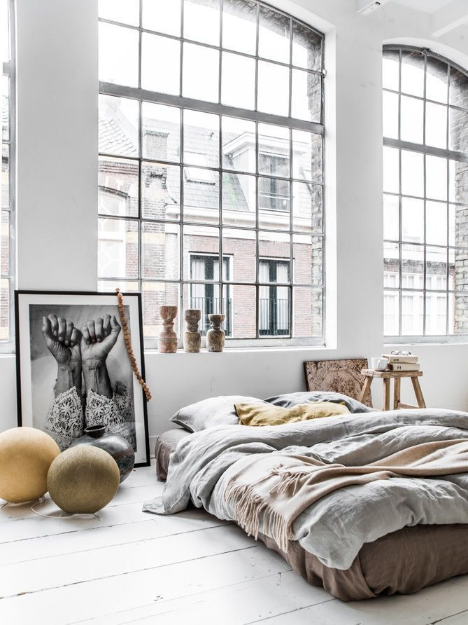 earthy brown bed linen gray duvet cover whitewashed wood plank floors huge glass windows with metal trims wood stool ornate vases and candles