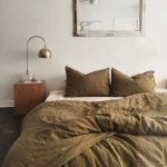 Earthy Tone Duvet Cover And Pillows White Bed Linen Square Shaped Wood Bedside Table Brass Desk Lamp