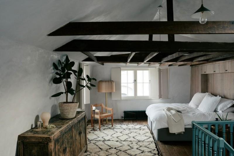 exposed wood beams white bedding treatment vintage rug worn out wood dressing potted houseplant wood corner chair floor lamp