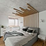 Gray Bed Frame With Headboard Light Gray Bed Linen And Duvet Cover Wood Floors Bare Concrete Ceilings White Walls Accented With Wood Panels