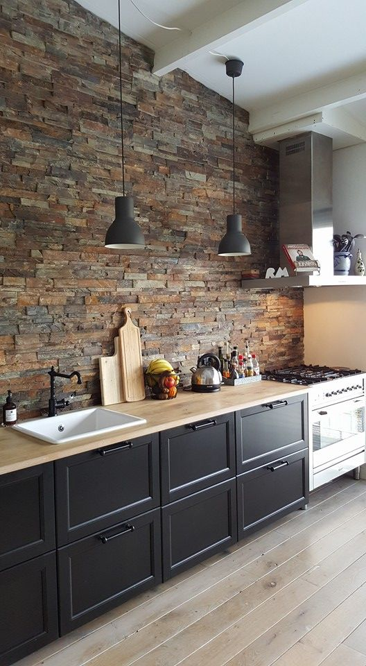industrial kitchen design brick walls and backsplash wood countertop black kitchen cabinets lighter wood plank floors stainless steel kitchen utensils