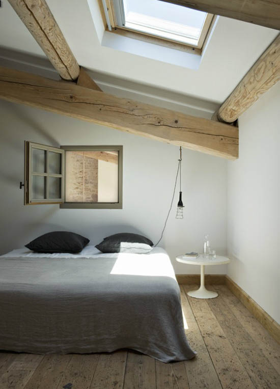 large sized wood beams skylight wood plank floors wood framed and trimmed interior window gray blanket white bed linen black pillows