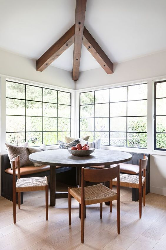 larger breakfast nook round top dining table dining chairs dark bench seat glass windows with black trims exposed wood beams