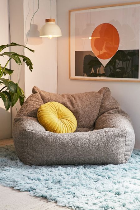legless loveseat in gray fluffy area rug in blue yellow throw pillow