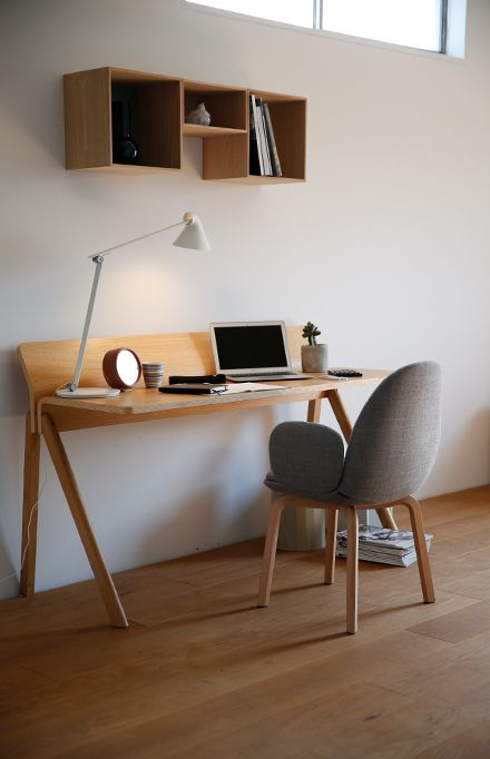 light wood working desk with wood panel addition and semi angled legs wood legged working chair with gray cushions gray back and gray armrests
