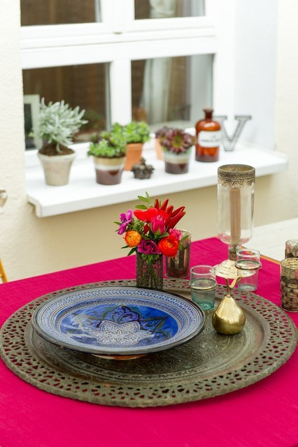 magenta tablecloth old look metal centerpiece antique plate dominated by deep blue glass cande holder brass tableware