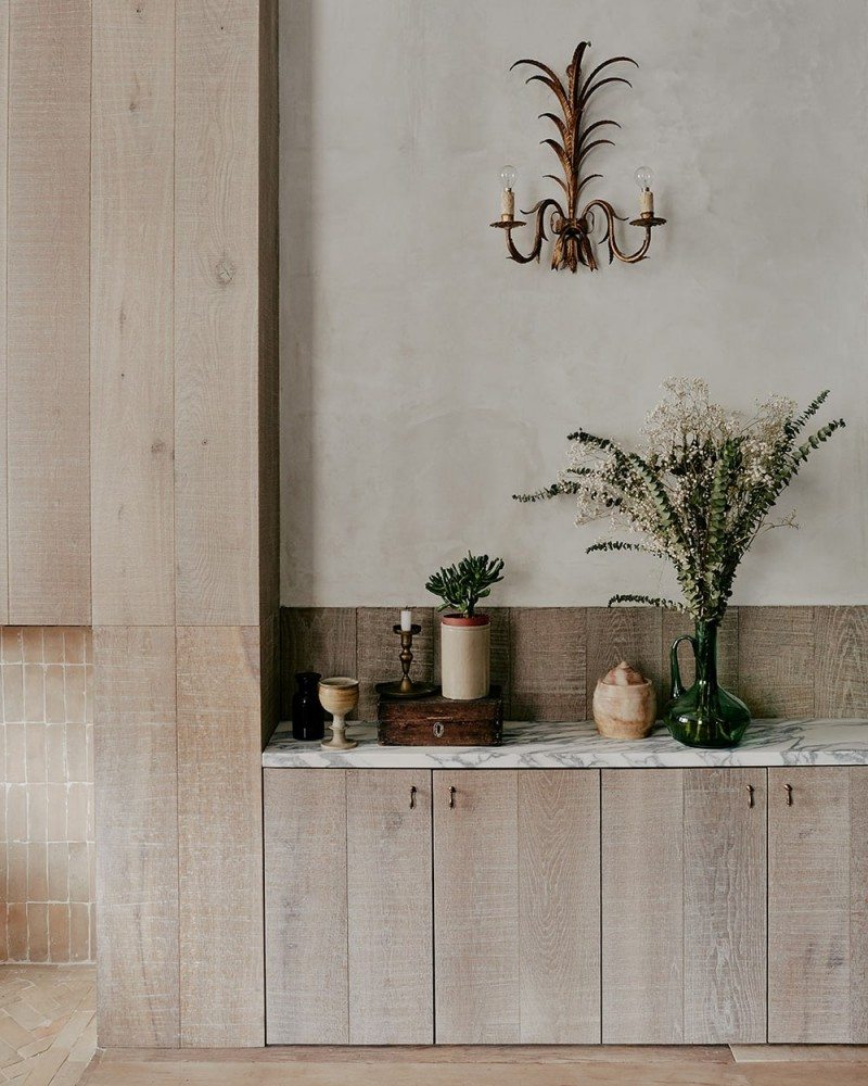 marble benchtop wood cabinets potted greenery concrete walls