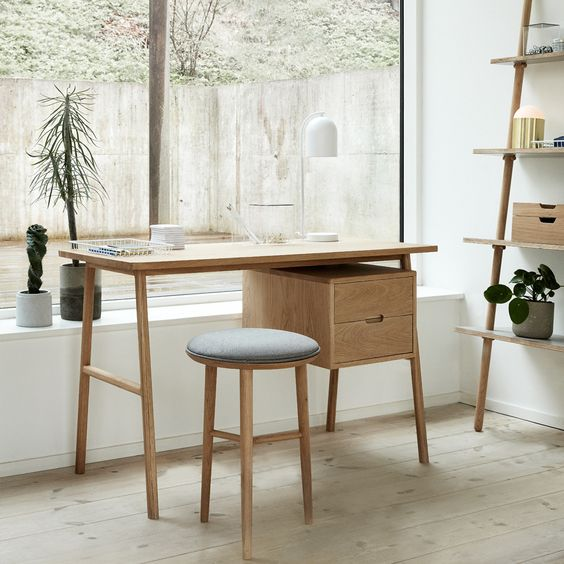 midcentury modern working table with under storage solution stool with light blue cushion and wood frame