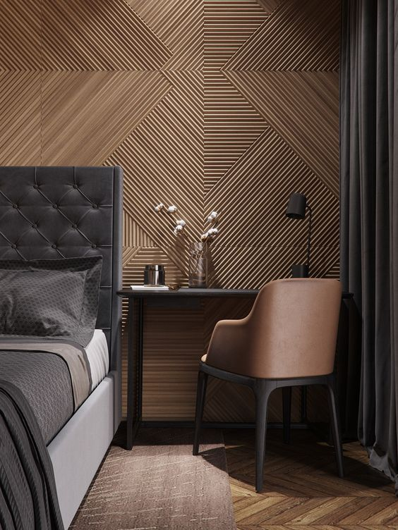 modern black bed frame with tufted heaboard herringbone patterned wood floors subtle herringbone patterned wall decals black side table dark earthy chair