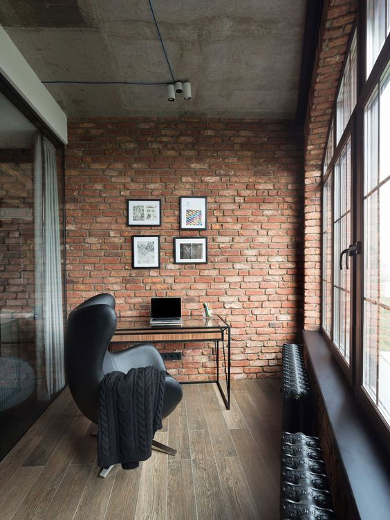 modern industrial workspace barely red brick wall raw concrete ceilings wood floors black leather chair glass working table