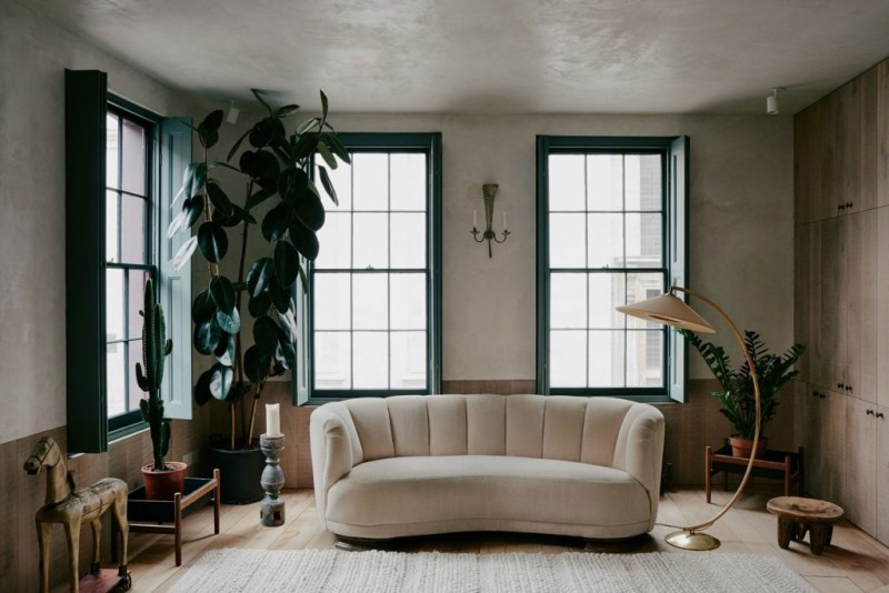 modern sofa in white unique floor lamp huge potted houseplant at the corner blue frames and trims on windows