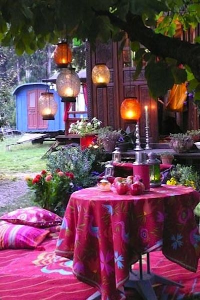 outdoor dining space in New Bohemian style deep pink carpet with floral motif deep pink tablecloth with botanical motifs
