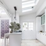 Oversized Tile Flooring In Earthy Tone White Mini Bar With Bar Stools And Bar Table Some Skylights