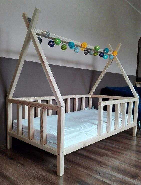 simple wood teepee bed frame with colorful ball decoration on top white mattress