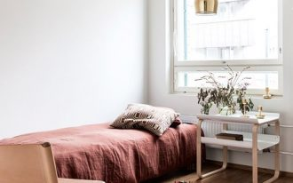 single bed frame rust bed linen wooden bedside table multicolored runner with fringed trims blush pink metal chair brass finish pendant