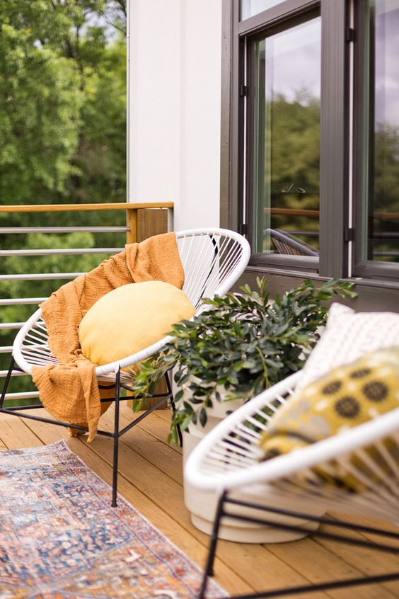 small balcony design a couple of egg lounge chairs with round throw pillow and yellow throw blanket shabby runner