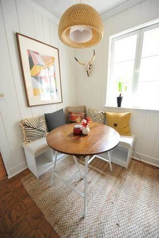 small breakfast nook L shaped bench seat in white colorful throw pillows round wood top table flat woven area rug oversized pendant with woven lampshade