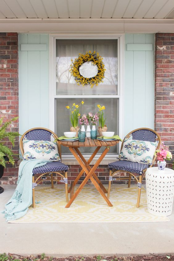 small porch idea navy blue chairs with rattan frame round top coffee table wih x base white side table aqua throw blanket yellow flower wreath