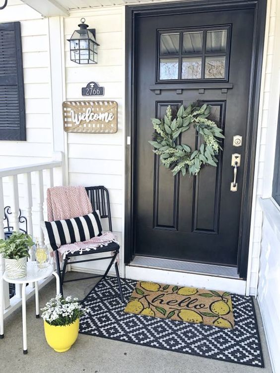 small spring porch refresh idea small chair in black striped throw pillow and blanket small white side table layered door mats flowers on yellow and white planters green wreath