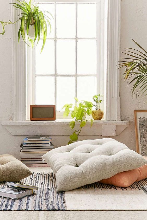 tufted floor pillows modern area rug a pile of books some greenery