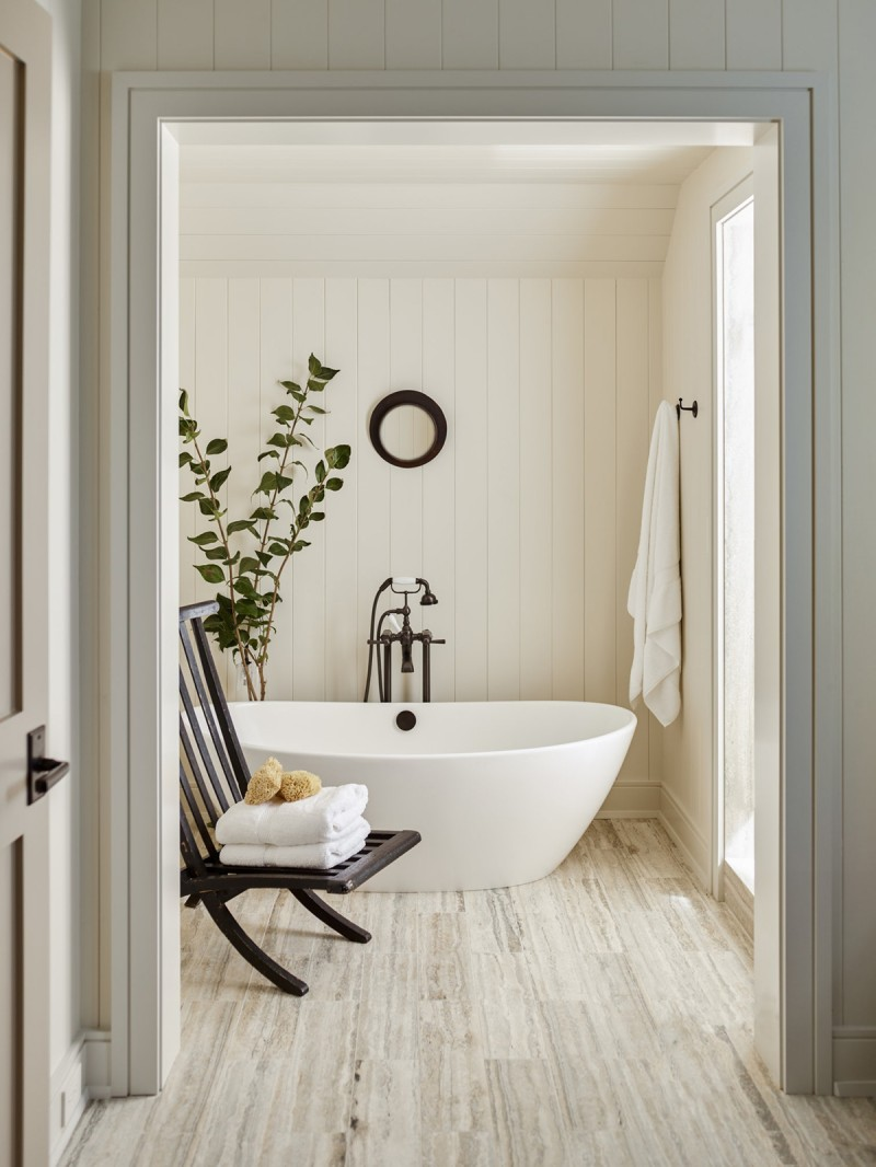 ultra soft toned bathroom light wood floors white wood plank walls modern white bathtub black wood chair