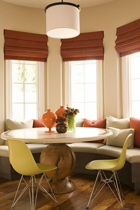vibrant color breakfast nook white round top table with wooden base pale yellow chairs semi round bench seat with colorful throw pillows