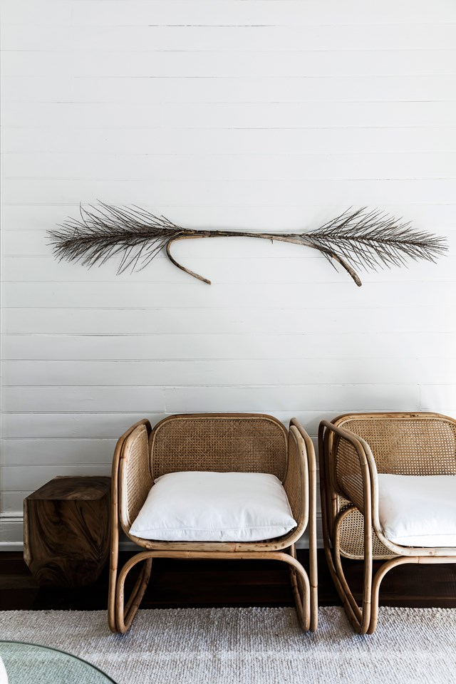 wall panelling in white dried branch for wall decor a pair of wicker chairs tree trunk side table white linen area rug